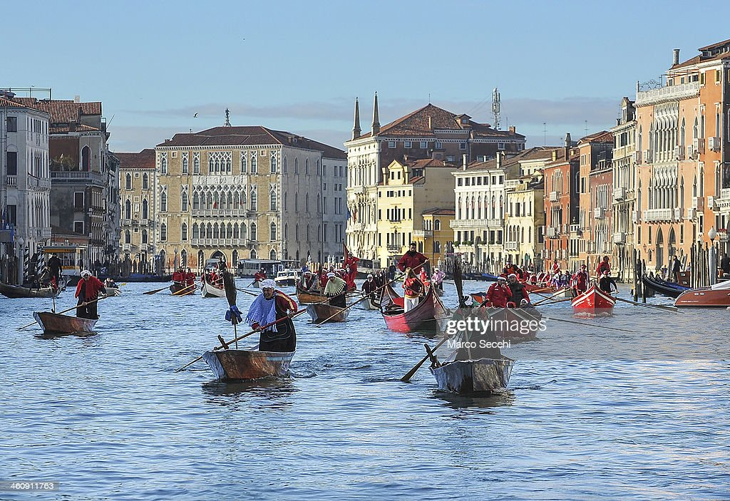 Rowers dressed in costume race along the Grand Canal for the 'Befana' Regatta on January 6 2014 in Venice Italy In Italian folklore Befana is an old...
