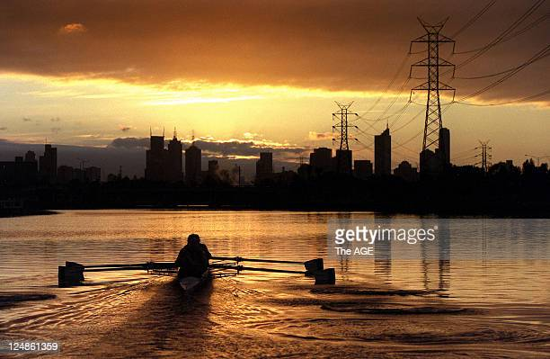 Rowers from the Essendon Rowing Club training on the Maribyrnong River at Ascot Vale Melbourne skyline at sunrise in the background November 13 2002