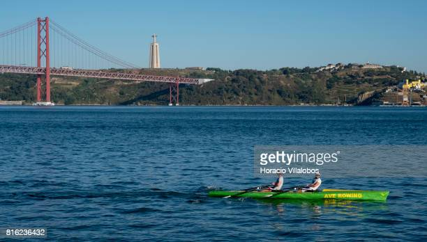 Rowers in an Ave Rowing boat pass by the Ponte 25 de Abril on July 14 2017 in Lisbon Portugal Although active all year round Portuguese tourist...