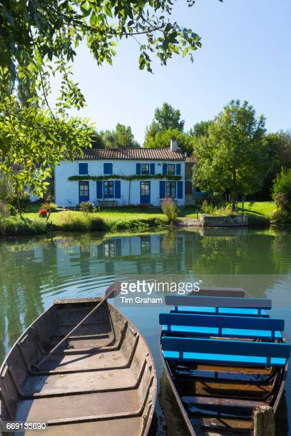 Rowing boats and house by River La SevreNiortaise in Coulon in Marais Poitrevin region Grand Site de France