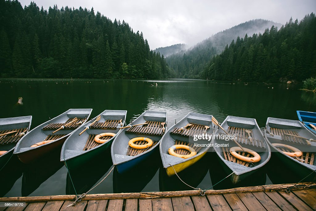 Rowing boats moored at the pier near mountain lake surrounded by misty forest