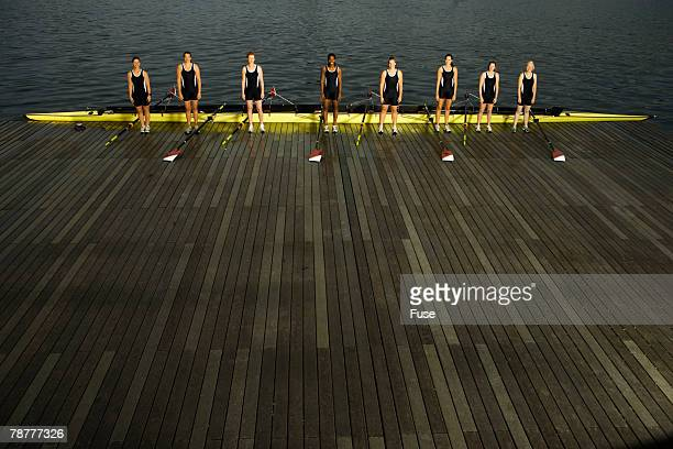 Rowing Crew Standing by Racing Shell on Jetty