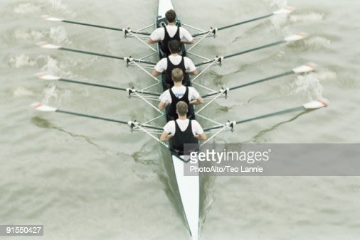 Rowing team rowing scull, oars out of water, high angle view