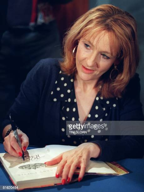 K Rowling author of the bestselling Harry Potter children's books autographs one of her works during a book signing 20 October 1999 in Washington DC...