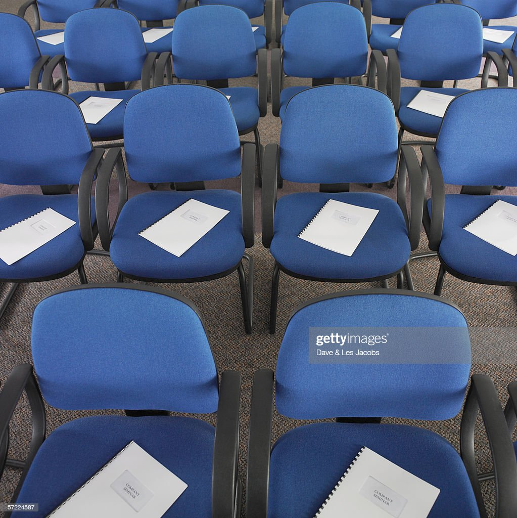 Rows of blue chairs with sheets of paper : Stock Photo