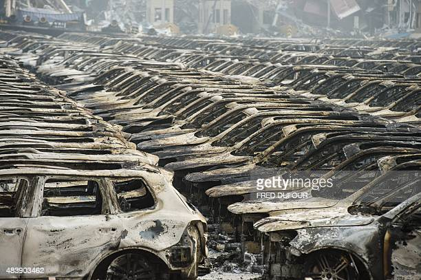 Rows of burnt out Volkswagen cars are pictured on the second morning after a series of explosions at a chemical warehouse hit the city of Tianjin in...