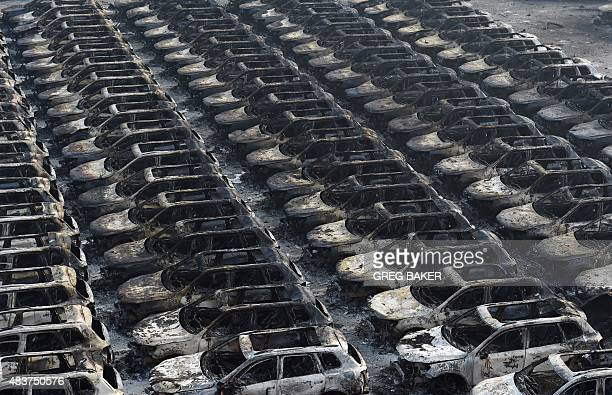 Rows of burnt out Volkswagen cars are seen near the site of a series of explosions in Tianjin northern China on August 13 2015 A series of massive...