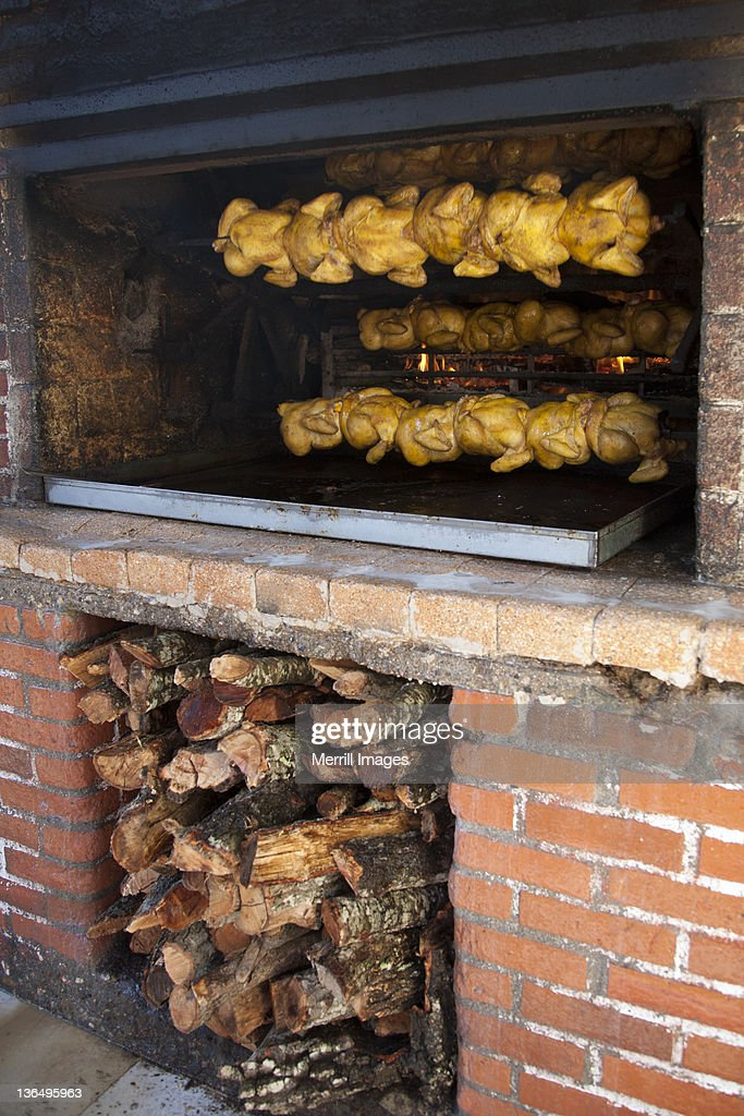 Rows of chicken roasting in wood oven : Stock Photo