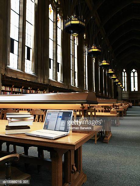 Rows of desks with laptop and books in university library