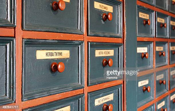 Rows of drawers of homeopathic herbs with 'Herba Thymi' (Thyme) in focus
