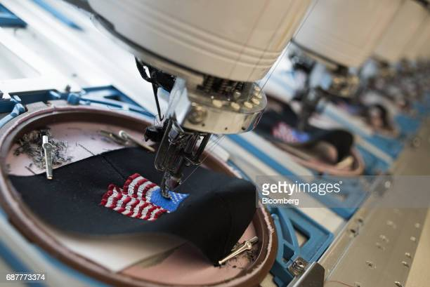 Rows of embroidery machines stitch an American flag design onto baseball hats at the Graffiti Caps production facility in Cleveland Ohio US on...