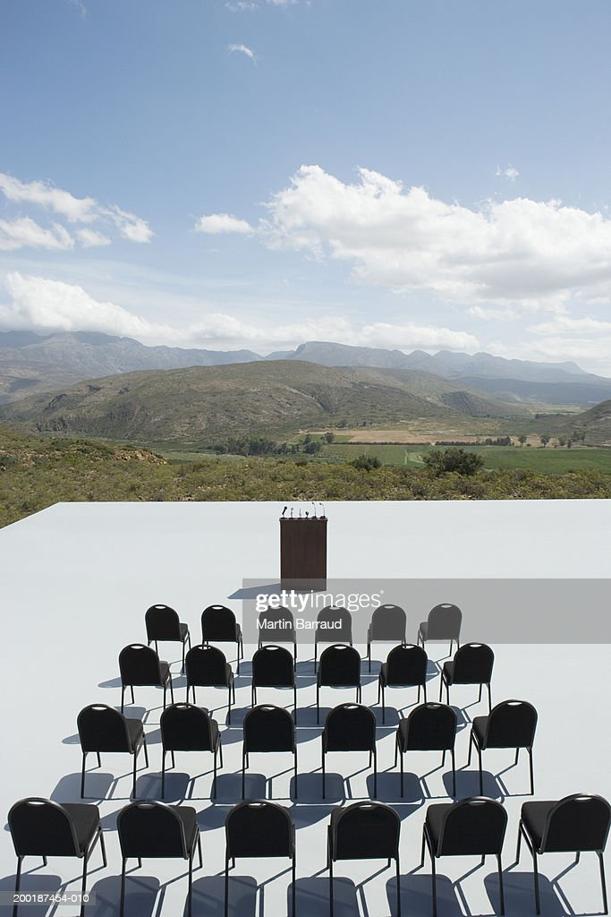 Rows of empty chairs and empty lectern, outdoors, elevated view