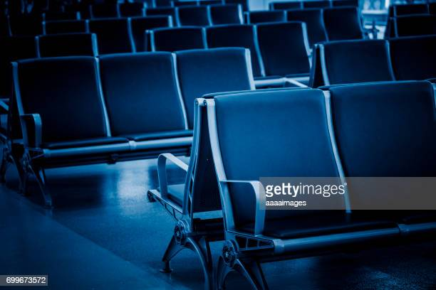 Rows of empty chairs at airport in blue tone