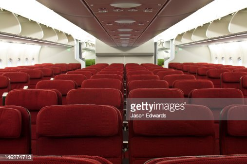 Rows of empty red economy class passenger seats in a plane cabin. : Stock Photo