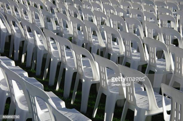 Rows of empty white plastic chairs arranged in readiness for an outdoor event