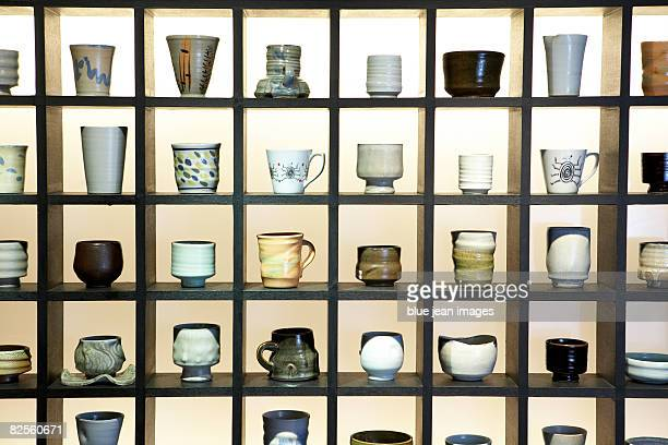 Rows of handmade cups and mugs on display.