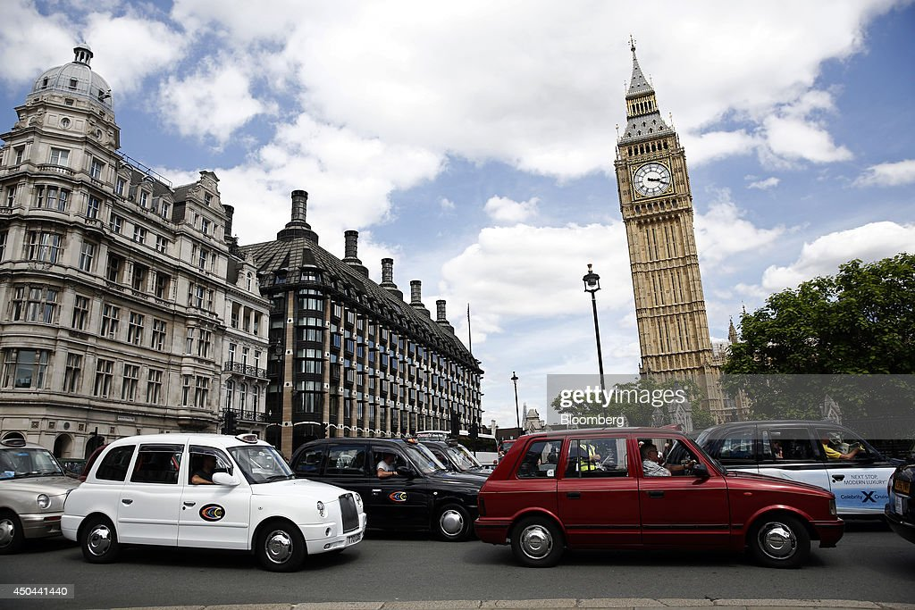 Rows of London taxi cabs stand parked outside Big Ben, right, and Portcullis House, center, during a protest against Uber Technologies Inc.'s car sharing service in London, U.K., on Wednesday, June 11, 2014. Traffic snarled in parts of Madrid and Paris today, with a total of more than 30,000 taxi and limo drivers from London to Berlin blocking tourist centers and shopping districts. Photographer: Simon Dawson/Bloomberg via Getty Images