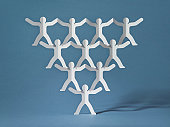 Rows of paper cut-out men balancing on one