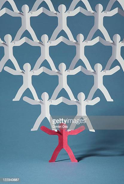 Rows of paper cut-out men balancing on one red