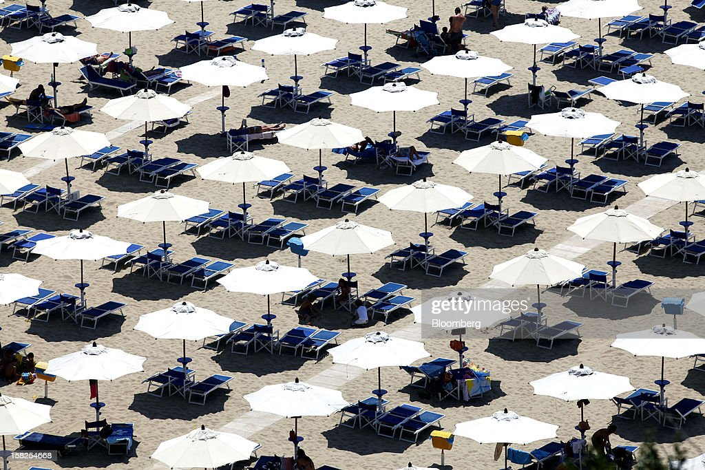 Rows of parasols and sun lounges are seen for hire in the coastal resort of Sperlonga, Italy, on Thursday, Aug. 2, 2012. Italy's economy shrank for a third straight quarter in the first three months of 2012 as the debt crisis worsened and Prime Minister Mario Monti's austerity measures pushed the country deeper into the recession, its fourth since 2001. Photographer: Alessia Pierdomenico/Bloomberg via Getty Images