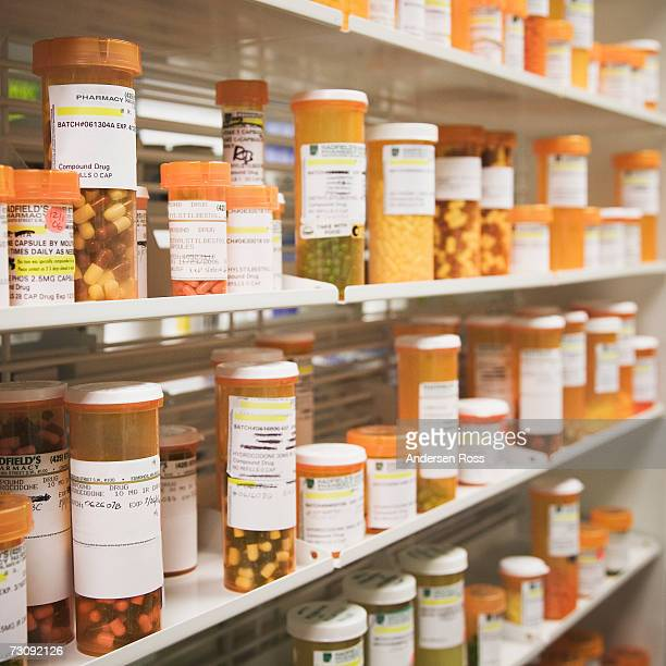 Rows of pill bottles on shelves in pharmacy, differential focus