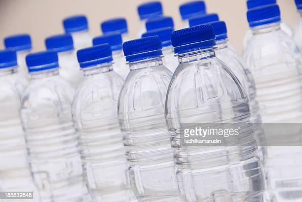 Rows of plastic water bottles with blue caps