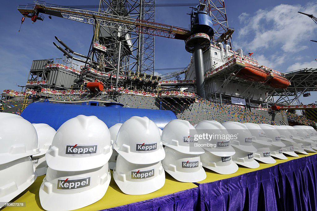 Rows of safety hats featuring the Keppel Corp. logo stand in front of the Transocean Andaman jackup rig, built for Transocean Ltd., during a naming ceremony at the Keppel FELS shipyard in Singapore, on Saturday, Feb. 2, 2013. Keppel Corp.'s FELS unit received a combined $1.5 million bonus for completing the construction of two drilling rigs ahead of time, the company said in a statement. Photographer: Munshi Ahmed/Bloomberg via Getty Images