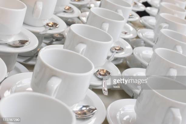 Rows of white cups and saucers