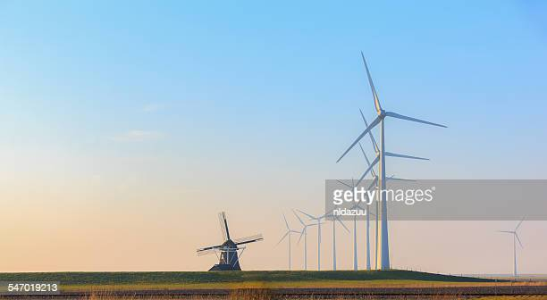 Rows of wind turbines and an old traditional windmill, Eemshaven, Groningen, Netherlands