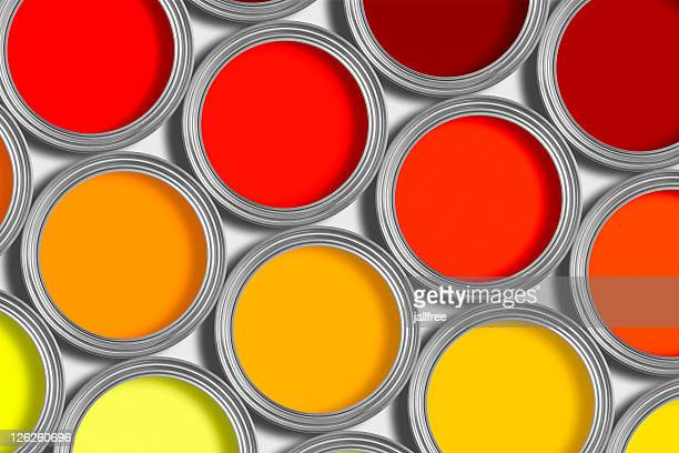 Rows or orange and red tins of paint on white