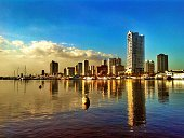Roxas Boulevard Reflected On Water Against Blue Sky