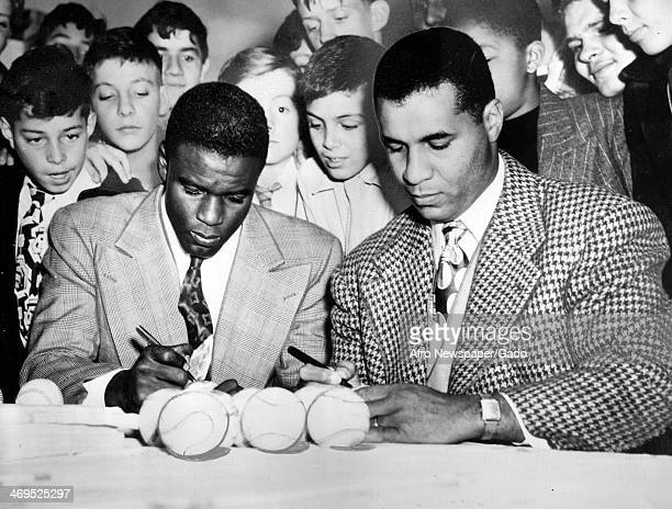 Roy Campanella catcher for the Brooklyn Dodgers and Jackie Robinson second baseman for the Brooklyn Dodgers sign autographs for children at Lincoln...