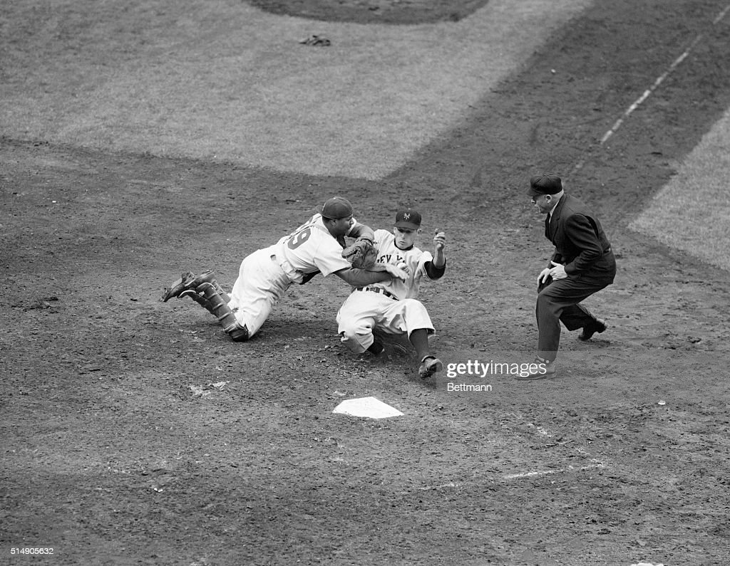 Roy Campanella tags out New York Giants rookie first baseman Jack Harshman as he tries to slide into home during a Giants-Dodgers game at Ebbets Field. Harshman tried to score on a pinch hit by Jack Maguire, but was gunned down at home by a Russell-to-Morgan-to-Campanella relay. Brooklyn defeated New York, 8-1.