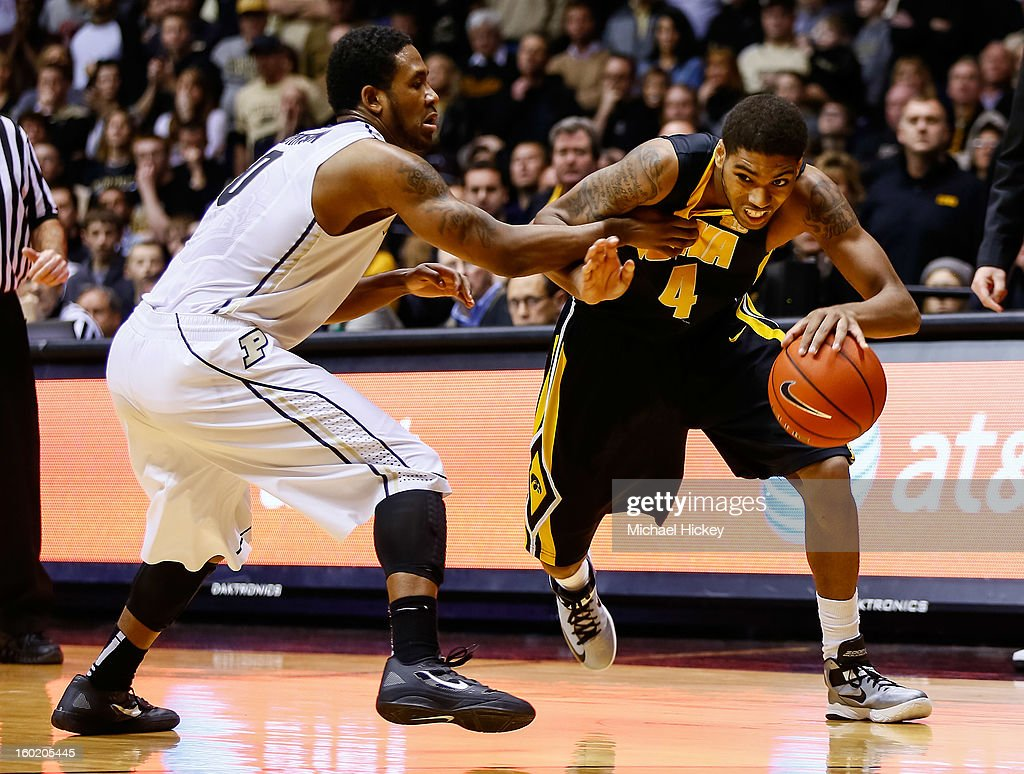 Roy Devyn Marble #4 of the Iowa Hawkeyes dribbles to the hoop as Terone Johnson #0 of the Purdue Boilermakers guards at Mackey Arena on January 27, 2013 in West Lafayette, Indiana. Purdue defeated Iowa 65-62 in overtime.