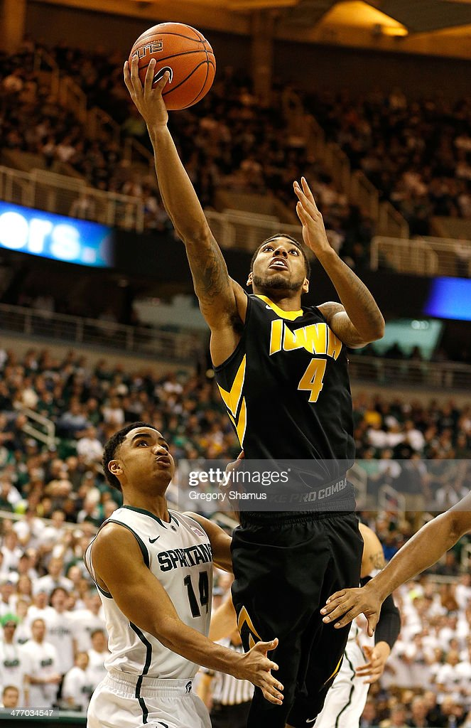 Roy Devyn Marble #4 of the Iowa Hawkeyes gets to the basket past Gary Harris #14 of the Michigan State Spartans during the first half at the Jack T. Breslin Student Events Center on February 6, 2014 in East Lansing, Michigan.
