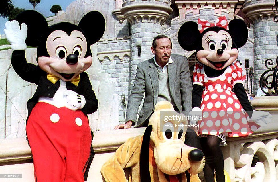 Roy Disney son of Walt Disney poses with Mickey Minnie and Pluto in front of the Sleeping Beauty castle during a press preview of the Euro Disneyland...