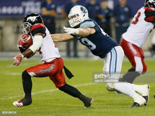 Roy Finch of the Calgary Stampeders tries outrun Jeffrey Finley of the Toronto Argonauts during a CFL game at BMO Field on August 3 2017 in Toronto...
