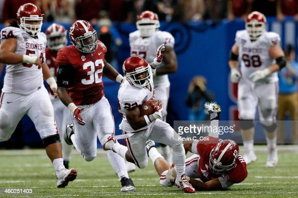 Roy Finch of the Oklahoma Sooners is tackled by Adrian Hubbard of the Alabama Crimson Tide during the Allstate Sugar Bowl at the MercedesBenz...