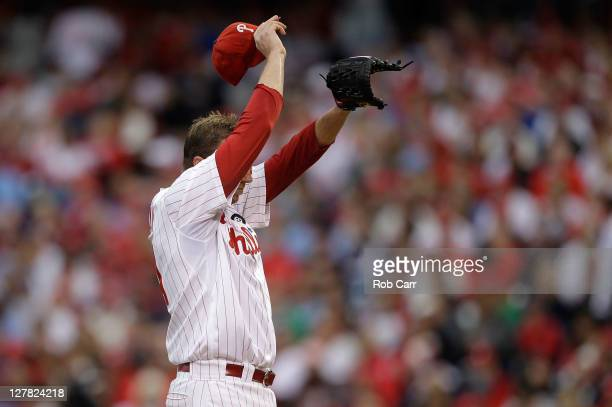 Roy Halladay of the Philadelphia Phillies reacts after allowing a threerun home run to Lance Berkman of the St Louis Cardinals in the first inning of...