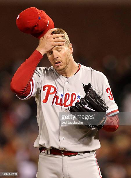 Roy Halladay of the Philadelphia Phillies wipes his brow after throwing a wild pitch in the fifth inning against the San Francisco Giants during an...