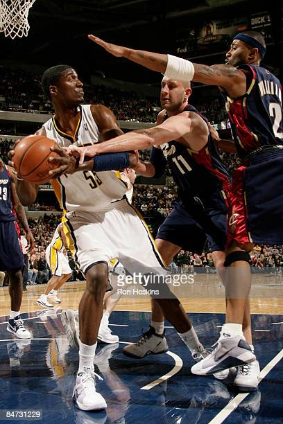 Roy Hibbert of the Indiana Pacers battles for the ball with Zydrunas Ilgauskas and Mo Williams of the Cleveland Cavaliers at Conseco Fieldhouse on...