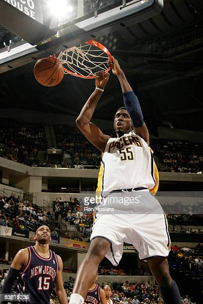 Roy Hibbert of the Indiana Pacers dunks past Vince Carter of the New Jersey Nets at Conseco Fieldhouse on November 8 2008 in Indianapolis Indiana...