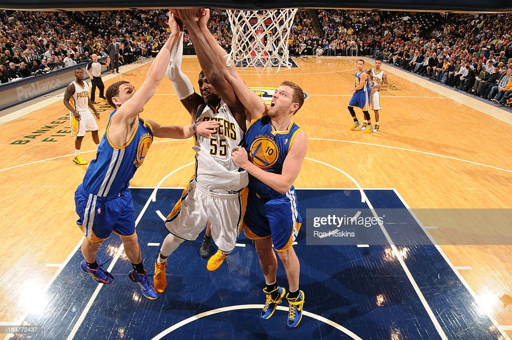 Roy Hibbert #55 of the Indiana Pacers goes up for a rebound against David Lee #10 and Klay Thompson #11 of the Golden State Warriors on February 26, 2013 at Bankers Life Fieldhouse in Indianapolis, Indiana.