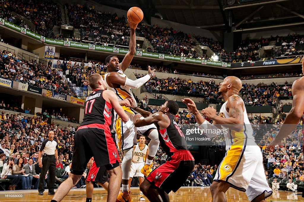 Roy Hibbert #55 of the Indiana Pacers passes the ball to teammate David West #21 against Amir Johnson #15 and Jonas Valanciunas #17 of the Toronto Raptors on February 8, 2013 at Bankers Life Fieldhouse in Indianapolis, Indiana.