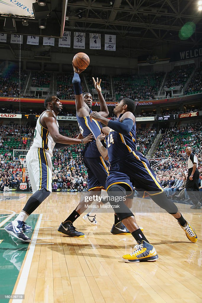 Roy Hibbert #55 of the Indiana Pacers passes to teammate Paul George #24 against Al Jefferson #25 of the Utah Jazz at Energy Solutions Arena on January 26, 2013 in Salt Lake City, Utah.