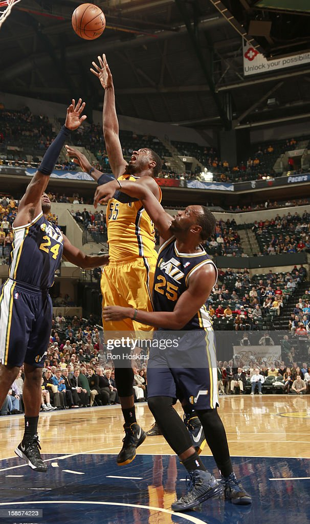 Roy Hibbert #55 of the Indiana Pacers sends the ball to the basket against Paul Millsap #24 and Al Jefferson #25 of the Utah Jazz during the game between the Indiana Pacers and the Utah Jazz on December 19, 2012 at Bankers Life Fieldhouse in Indianapolis, Indiana.
