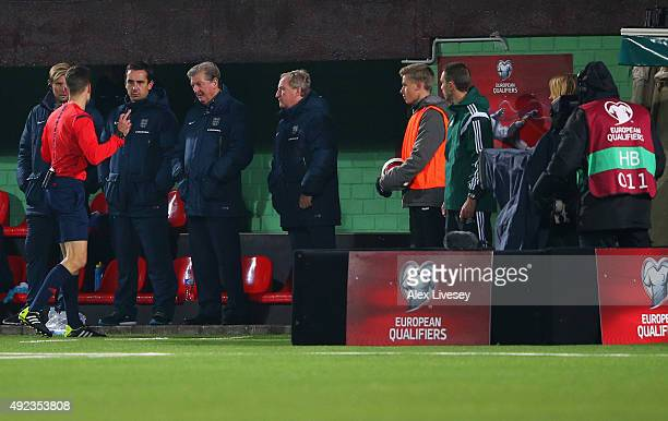 Roy Hodgson manager of England and the team bench query the positioning of a TV camera with referee Kenn Hansen during the UEFA EURO 2016 qualifying...