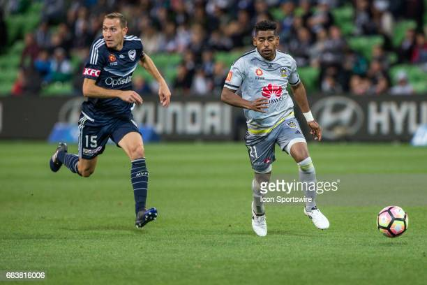 Roy Krishna of the Wellington Phoenix chases down the ball in front of Alan Baro of Melbourne Victory during the round 25 match of the Hyundai...