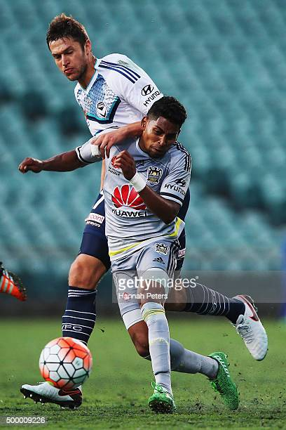 Roy Krishna of the Wellington Phoenix competes for the ball with Matthieu Delpierre of the Melbourne Victory during the round nine ALeague match...
