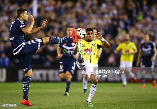 Roy Krishna of Wellington Phoenix is challenged by Matthieu Delpierre of Melbourne Victory during the round four ALeague match between the Melbourne...